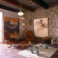 A living room with a beamed ceiling, exposed stone wall and tiled floor. The room is furnished with retro style furniture and contemporary paintings hang on the walls.