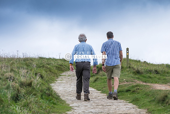 Walkers on the South West Coastal Path at Carnewas at Bedruthan in Cornwall.