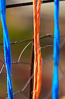 Colorful strands of orange and blue twine hang from the side of a chickenwire garden fence.