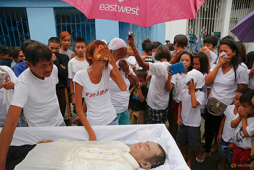 Diane Agregado, the daughter, and other relatives of Reynaldo Agregado, who was killed in a police anti-drugs operation, mourn over his body during the funeral in Manila, Philippines October 15, 2016. REUTERS/Damir Sagolj