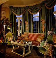 Opulent green swagged damask curtains with gold tassels dominate the bay window of the drawing room