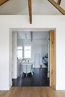 A sliding wooden door opens onto a slate-tiled contemporary bathroom
