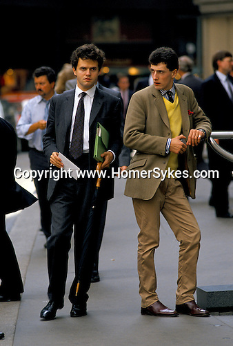 THE CITY OF LONDON, TWO MEN  OUTSIDE LLOYDS OF LONDON. 1992. 1990S DRESS DOWN FRIDAY, WAS THE NAME GIVEN TO THE  RELAXATION OF THE TRADITIONAL DRESS CODE FOR BUSINESSMEN. THEY WERE ALLOWED AND ENCOURAGED TO WEAR INFORMAL CASUAL CLOTHES TO THE OFFICE.  THIS WAS SUPPOSED TO HELP WITH OFFICE BONDING AND ENCOURAGE  CAMARADERIE.