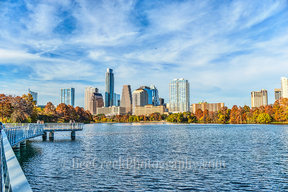 This photo of the Austin skyline from the boardwalk hike and bike trail over Ladybird Lake is a great place to see the city skyline.  You are able to see the city building as they crowd along  the shore of town lake  from this location, but just about anywhere along the hike and bike trail you can get a good view.  Austin is a very modern city with lot of activities going on daily, and in some people view maybe a bit too much but then who asking.  There is always an event, or a race or something else going on in the parks so alway find out what is going on because parking can be nightmare .  This photo was catured in December so the tree had turned these nice fall colors with the backdrop of the city and the nice blue skies it was a lovely day.
