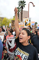 Phoenix, Arizona. April 25, 2012 - A young woman demonstrator chants outside of the ICE building on Central Avenue. About 500 people protested the controversial law on the same day U.S. Supreme Court justices heard legal arguments on the Arizona vs. United States case. At the end of the march, six activists blocked Central Avenue by sitting in the middle of the street. They all were arrested by the Phoenix Police Department and taken to the Fourth Avenue County Jail. Photo by Eduardo Barraza © 2012