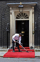 Cleaner hoovers the carpet outside Number 10 Downing Street, the home of the British Prime Minister, London, United Kingdom