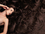 Beautiful woman with very long brown hair and hair extensions. Large copyspace or background.