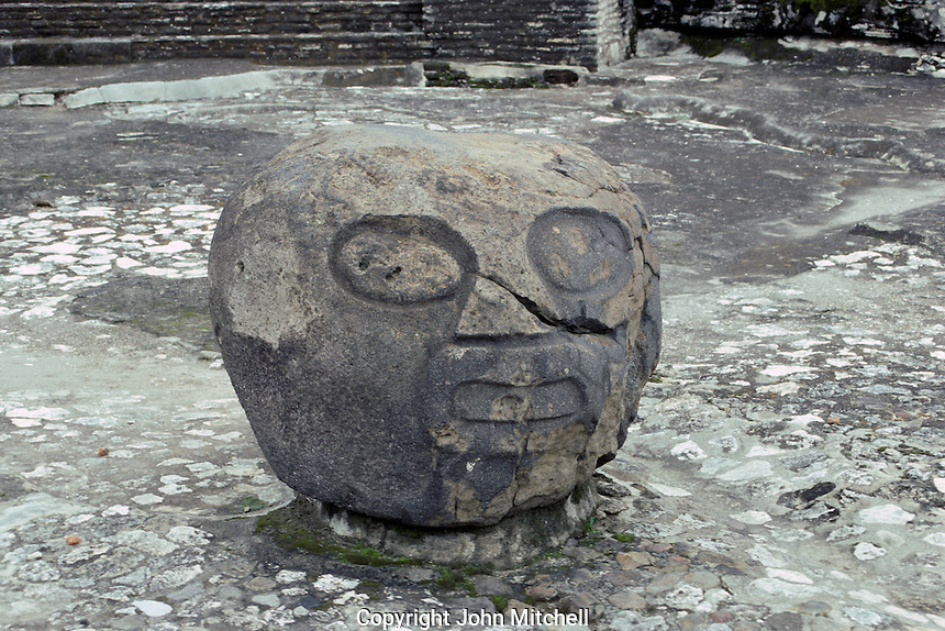 Pre-Columbian stone head in the Patio de los Atares or Patio of the Altars. Archaelogical Zone, Cholula, Puebla, Mexico