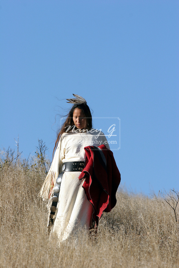 A Native American Indian woman with a red blanket in the prairie of South Dakota
