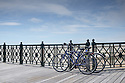 "Two bicycles lean against the railings on Hastings Pier. The pier has recently (April 2016) been reopened after extensive rebuilding owing to a fire razing it to the ground in 2010. The council compulsorily purchased it from its owners in 2012, and the so-called ""people's pier"" is now in the hands of the Hastings Pier Charity and more than 3,000 shareholders, who bought into the project at £100 a share."