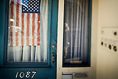 Stars and stripes of a national flag in a front door window