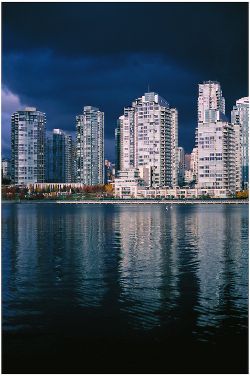 Condominium towers of the North shore of False Creek, casting reflections during a brief break of sunlight through dark, heavy clouds of a winter rain storm, Vancouver, BC.