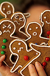 Gingerbread cookies with mad/angry/surprised faces, reacting to the hectic pace at Christmas/Holiday times, focus on faces with woman holding them up