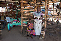 Africa, S. Sudan, Juba<br /> South Sudan gained its independence from Sudan in 2011 and many still live in what seems to be temporary housing. It&rsquo;s a dry sparse land with little ability for rural agriculture. Mary Sebit (28) is a goat herder. The non-governmental organization, BRAC, gave her mature goats that have now produced young goats. She has five children and she'll sell one goat a year for about $125 to send each of her kids to school. Her husband works as a policeman. She is here with her mother (50) who is ill and lives with them.