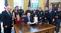 United States President Donald J. Trump, surrounded by men and women in uniform, about violence against police and signs a proclamation supporting police officers at The White House in Washington, DC, May 15, 2017.  US Vice President Mike Pence looks on from left.<br /> Credit: Chris Kleponis / Pool via CNP /MediaPunch