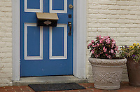 Mail box on colorful blue and white door. Large ceramic flower pots.
