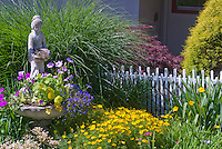 Oriental woman figure statue, ornamental Miscanthus grass, Coreopsis yellow flowers, Astilbe pink blooms, white picket fence, Japanese maple Acer palmatum, evergreen tree, house, container planter of petunias, lobelia, nasturtiums