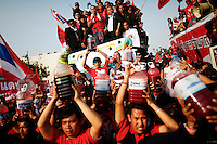 """Supporters of former premier Thaksin Shinawatra hold canisters with human blood before pouring it outside the Government house in Bangkok March 16, 2010. Thousands of protesters in Thailand donated blood and poured it later outside the premier's office on Tuesday, a """"sacrifice for democracy"""" aimed at energising their movement after the government refused to step down.   REUTERS/Damir Sagolj (THAILAND)"""