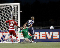 New England Revolution goalkeeper Preston Burpo (24) dives to save a shot at goal with FC Dallas midfielder/forward Atiba Harris(16) and New England Revolution defender Darrius Barnes (25) in position to intercept the ball.  The New England Revolution drew FC Dallas 1-1, at Gillette Stadium on May 1, 2010