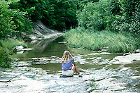 Young woman 25-30 years old sits beside Grindstone creek in sumertime, Midwest USA