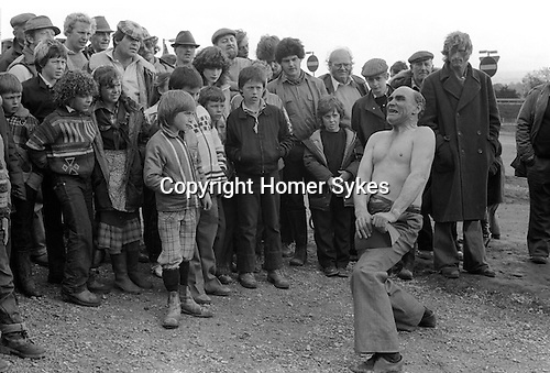 Appleby in Westmorland. 1981  <br /> Johnny Eagle the famous gypsy strongman, showman and escapologist tearing book in half.