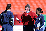 """16 October 2004: U.S. coach April Heinrichs (center) with Shannon Boxx (left) and Angela Hucles (right). The United States defeated Mexico 1-0 at Arrowhead Stadium in Kansas City, MO in an women's international friendly soccer game as part of the U.S.'s """"Fan Celebration Tour.""""."""