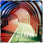 Interior of a road crossing walkway with bright red arched design and slow lane