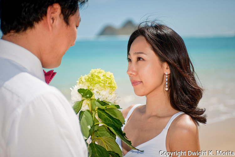 Asian bride gazes at husband on Lanikai beach as the couple looks forward to their life as a married couple following their wedding.