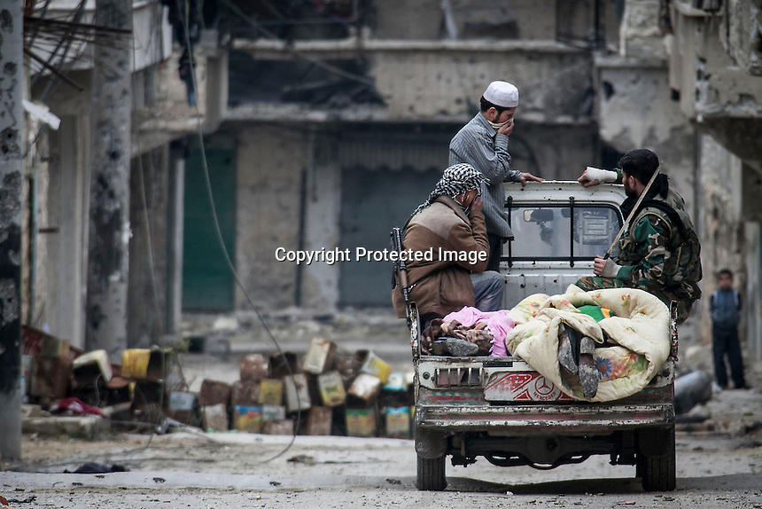 In this Monday, Dec. 10, 2012 photo, two dead bodies are taken away from the battlefield after they were discovered allegedly executed and abandoned inside a residential house in Aleppo, Syria. (AP Photo/Narciso Contreras)