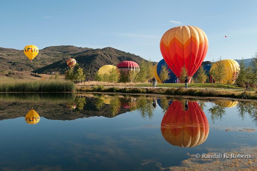 Hot air balloons float over pond, Snowmass balloon festival, Colorado
