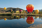 Hot air balloons float over pond, Snowmass balloon festival, Colorado