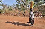 A woman carries water home in the Southern Sudan village of Kupera. The well where she obtained the water was installed by Catholic Relief Services (CRS). Families here returned from refuge in Uganda in 2006 following the 2005 Comprehensive Peace Agreement between the north and south.