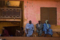 Mopti, Mali, 2009 - A group of elderly men avoid the mid-day heat by resting in the shade of a  dilapidated office building in the regional trading town of Mopti.