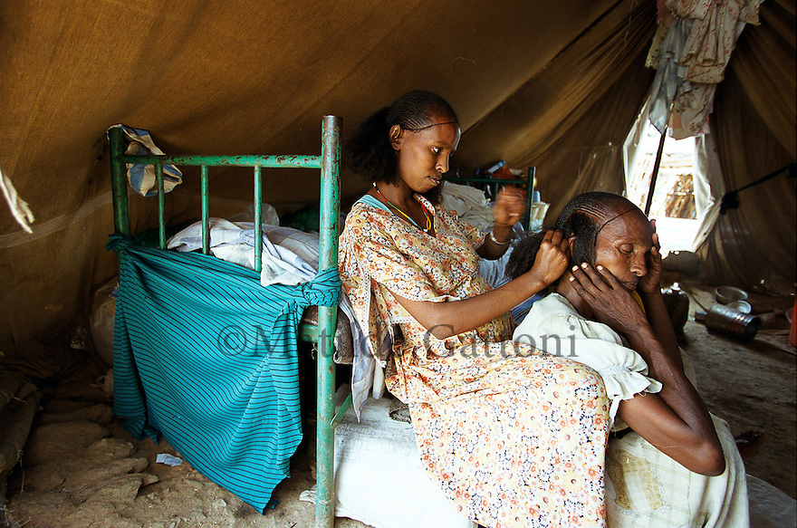 Eritrea - Debub- Mother and daughter taking care of eachother. As a result of 30 years of war for independence against Ethiopia (from 1961 to 1991) and another 3 years from 1997 to 2000, there are 50,000 Eritreans currently living in internally displaced (IDP) camps throughout the country. These IDPs have fled three times in the last 10 years, each time because of renewed military conflict. They lived in relatives' homes when lucky enough, but mostly, the fled to the mountains, where they attempted to do what Eritreans do best, survive. Currently there is no Ethiopian occupation in Eritrea, but landmines prevent the IDPs from finally going home. .It is estimated that every Eritrean family lost two or three members to the war which makes the reality of the current emergency situation even more painful for Eritreans worldwide. Currently, the male population has been decreased dramatically, affecting the most fundamental socio-economic systems in the country. Among the refugee population, an overwhelming majority of families are female-headed, severely affecting agricultural production. For, IDPs in particular, 80% of households are female-headed..The unresolved border dispute with Ethiopia remains the most important drawback to Eritrea's socio-economic development, as national resources (human and material) continue to be prioritized for national defense. Eritrea is vulnerable to recurrent droughts and variable weather conditions with potentially negative effects on the 80 percent of the population that depend on agriculture and pastoralism as main sources of livelihood. The situation has been exacerbated by the unresolved border dispute, resulting in economic stagnation, lack of food security and increased susceptibility of the population to various ailments including communicable diseases and malnutrition..