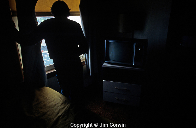 Man standing in front of window in a downtown motel room