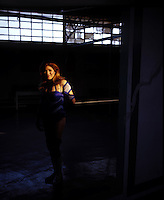 "A ""luchadora"" (women wrestler) poses for a photograph in the ""Gymnasio Latinoamericano"" a well known gym for male and female boxers and luchadores in the Center of Mexico City. August 2004"