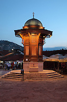 The Sebilj at night, a public fountain in Ottoman style made from wood on a stone base, built 1891, in Bascarsija Square, Sarajevo, Bosnia and Herzegovina. The square is also called Pigeon Square as people sit in the cafes drinking coffee and feeding the many pigeons which congregate here. The city was founded by the Ottomans in 1461. Picture by Manuel Cohen