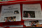 Uniontown, Pennsylvania.USA.October 23, 2004..Two newspapers on a news stand : one with a photo of Bush greeting a crowd in Penn as he campaigns for re-election and another of a funeral of a US soldier who was killed in Iraq ... being buried in another part of Penn.