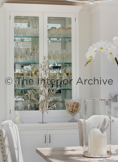 Glass-fronted cabinets displaying collections of glassware line the walls of the dining room