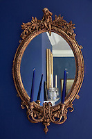 A gilt-framed mirror reflects the ornaments on the mantelpiece in the dining room