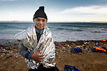 A refugee from Afghanistan stands on a beach near Molyvos, on the Greek island of Lesbos, on October 31, 2015. He arrived on a boat full of refugees from Turkey. They were received by local and international volunteers, then proceeded on their way toward western Europe. The boat was provided by Turkish traffickers to whom the refugees paid huge sums to arrive in Greece.