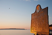 Mackinac Island historical marker and Lake Huron at St. Ignace Michigan at dawn.