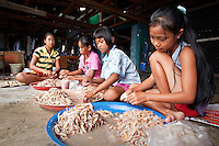 Girls in a  Cambodian fishing village help process the day's catch