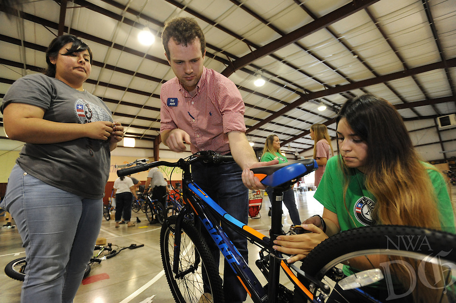 NWA Democrat-Gazette/ANDY SHUPE<br /> Daniela Alvarado (left) and Denise Bravo (right), both Americorps volunteers, work with Ray Ford (center) of Arvest Bank Friday, Sept. 11, 2015, as they assemble a bicycle at John Tyson Elementary School in Springdale. Volunteers assembled the last 32 bikes of a total 850 bikes funded by a grant from the Walton Family Foundation.
