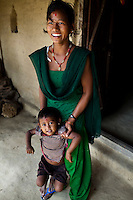 Pramila Tharu, 15, carries her 2 year old toddler Prapti as she stands at the door of her home in Bhaishahi village, Bardia, Western Nepal, on 29th June 2012. Pramila eloped and married at 12 and gave birth to Prapti at age 13. She delivered prematurely on the way to the hospital in an ox cart and her baby weighed only 1.5kg at birth. In Bardia, StC works with the district health office to build the capacity of female community health workers who are on the frontline of health service provision like ante-natal and post-natal care, especially in rural areas. Photo by Suzanne Lee for Save The Children UK