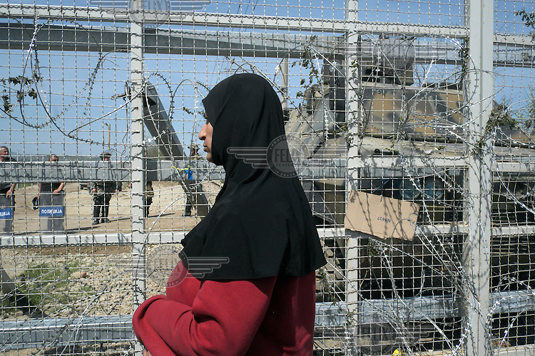 A refugee woman, from the makeshift refugee camp at Idomeni, stands in front of a razor wire fence on the Greek-Macedonian border. Scores of women cut through the fence and settled in front of Macedonian border demanding that the borders be opened. Around 14,000 people were stranded in the camp which the authorities have since closed and distributed the occupants among several official camps around the country.