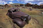 A rusted car sits in the historic ghost town of Bodie, CA