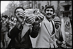 Men hold an Iranian rial bank note with the cut out face of the Shah replaced by that of  Ayatollah Khomeini's. Tehran, January 16, 1979.