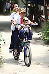 Three schoolboys ride a bicycle down an alley in Hue, Vietnam. April 22, 2013.