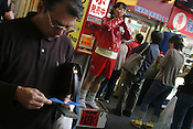 "A man checks his lottery tickets after purchaing them at a booth which is menat ot be ""luckier"" than others. A woman, in red, shouts ot advertise the sale of the lottery tickets. Tokyo, Japan"